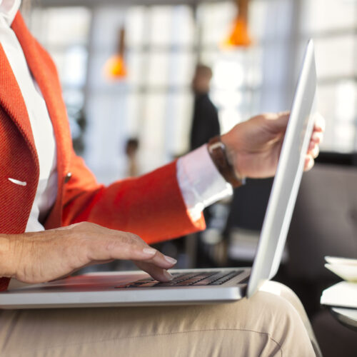 Midsection of businesswoman using laptop in restaurant